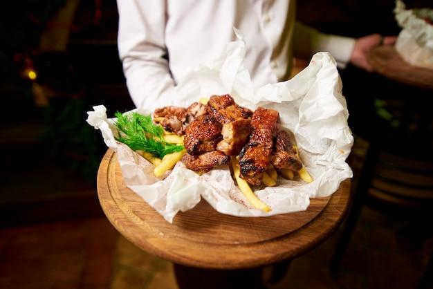 Жареные ребрышки с картошкой и зеленью на деревянном подносе в руке официанта