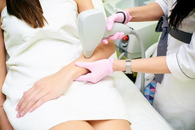美容師は女の子の体からレーザー脱毛の手順を実行します。レーザー脱毛。宇宙学