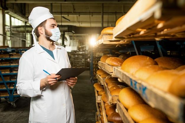 パン。パンの生産ライン。制服を着た男。衛生チェック。