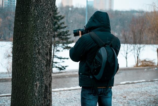 Мужчина в куртке с капюшоном и портфелем на спине, держит фотоаппарат и фотографирует дерево
