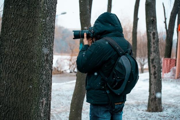 カメラを抱えて木の写真を撮る、フードと背中にブリーフケースをかぶったジャケットの男