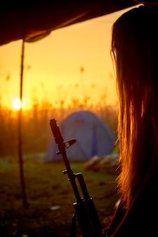 日の出の背景に彼の手に銃を持つ少女のシルエット