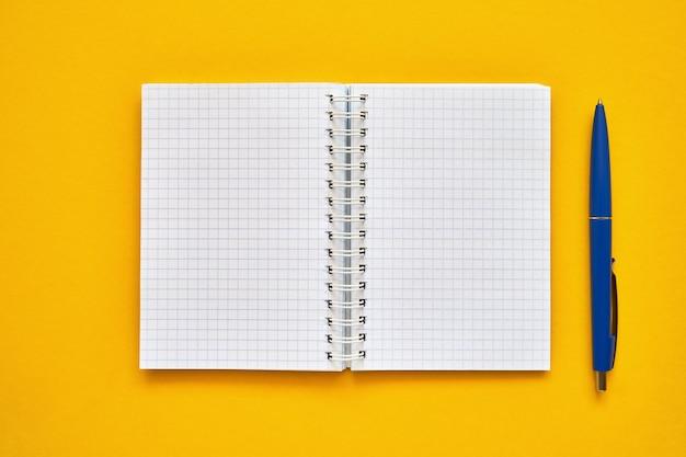 空白の四角いページと青ペンで開いているノートブックの平面図。黄色の背景、スパイラルメモ帳に学校のノート。学校概念に戻る