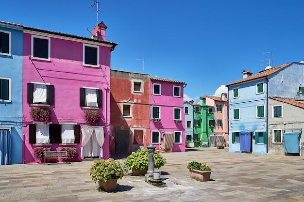 Бурано, венеция. архитектура старинных красочных домов на площади с фонтаном