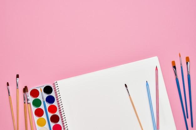 パステルピンクの鉛筆でスパイラルメモ帳。学校概念に戻る。コピースペース、トップビュー。