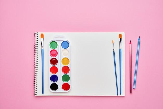 パステルピンクの水彩絵の具でスパイラルメモ帳。学校概念に戻る。コピースペース、トップビュー。