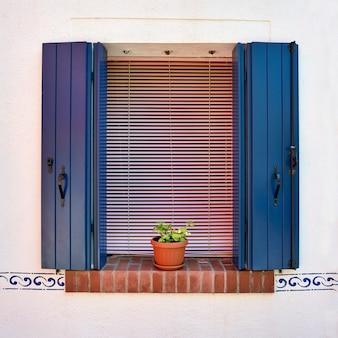 Окно с открытыми синими ставнями и цветами в горшке.