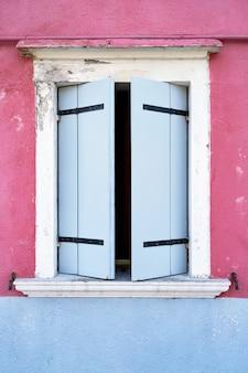 Окно с голубым затвором на розовой стене.