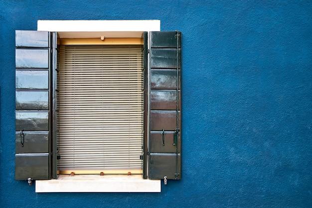 Окно с зелеными ставнями на синей стене домов.
