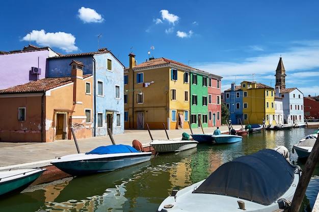 Бурано, венеция. разноцветные дома, канал острова бурано и лодки.