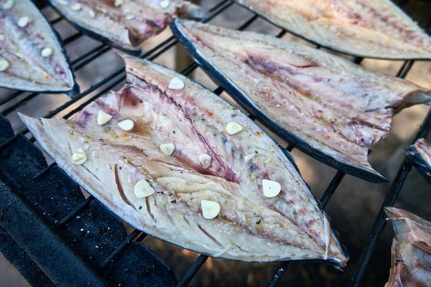 Процесс копчения рыбы. копченая скумбрия с чесноком. закройте курение. выборочный фокус