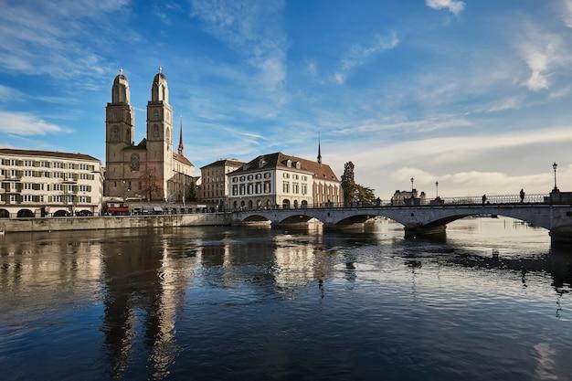 チューリッヒの歴史的な街の眺め。グロスミュンスター教会とスイスのリマト川を渡るミュンスターバック。