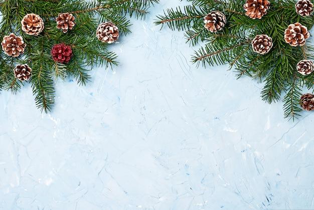 青色の背景にコーンとクリスマスのモミの木の枝。コピースペース