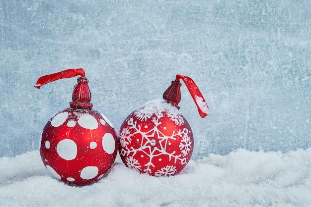 雪の中で赤いクリスマスボール。クリスマスの背景。コピースペース