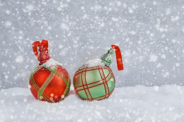 雪の中で赤と緑のクリスマスボール。クリスマスの背景。コピースペース