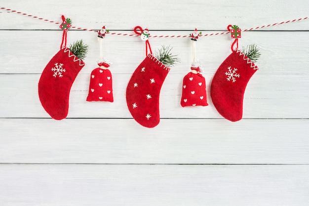 赤いクリスマスソックスと白い木製の背景にギフトバッグ。コピースペース