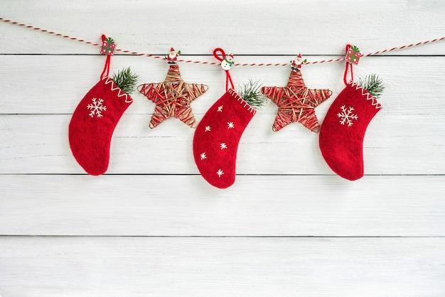 赤いクリスマスソックスと白い木製の背景の星。コピースペース