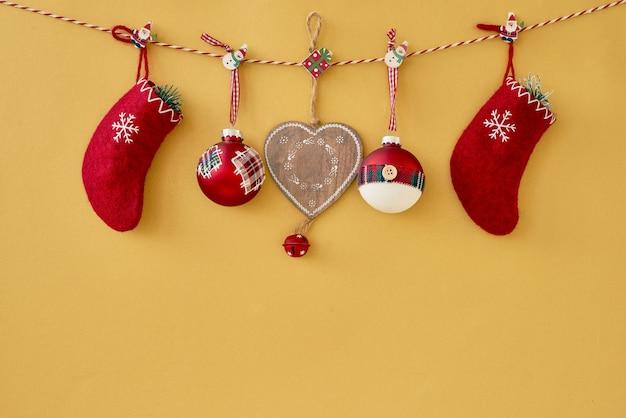 クリスマスの背景。黄色の背景に赤のクリスマスの装飾。コピースペース