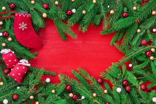 赤いクリスマス背景。クリスマスツリーの枝、ギフト、赤いクリスマスソックス。コピースペース