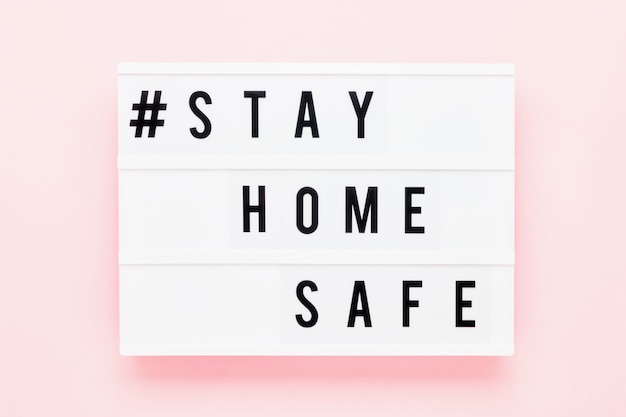 Оставайтесь домашним безопасным, написанным в светлой коробке на розовом фоне. здравоохранение и медицинская концепция. вид сверху. карантинная концепция.
