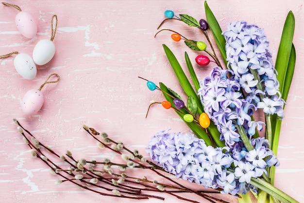 花と装飾的な卵のイースターの背景。トップビュー、コピースペース