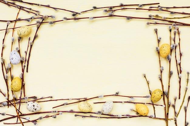 イースターの背景。柳の枝と装飾的な黄色の卵の境界線。コピースペース、トップビュー