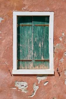 赤い壁に古い緑の緑のシャッターが閉じたウィンドウ。イタリア、ベニス、ブラーノ島。