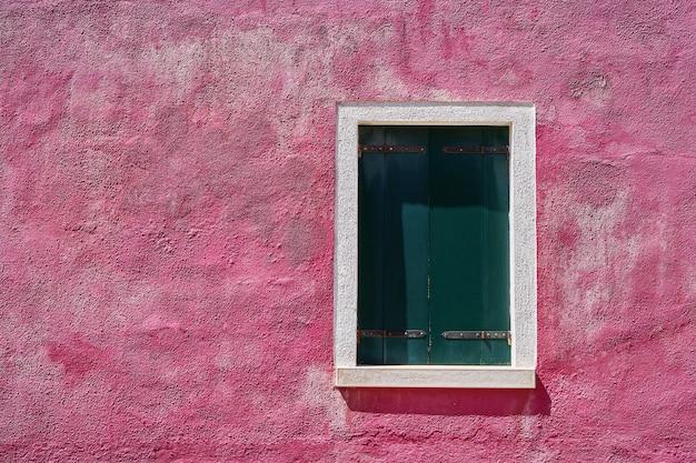 明るいピンクの壁に緑の緑のシャッターが閉じたウィンドウ。イタリア、ベニス、ブラーノ島。