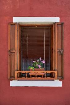古い木製のシャッターと鍋にピンクの花を持つウィンドウ。イタリア、ベニス、ブラーノ