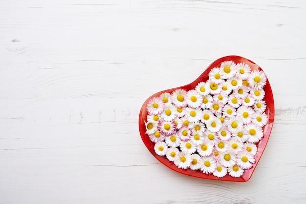白い木製の背景にデイジーの花から大きな心。コピースペース、上面図。休日の背景
