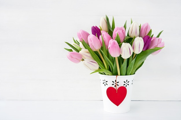 赤いハートの白い花瓶にピンクと白のチューリップの花束。バレンタインデーのコンセプトです。コピースペース