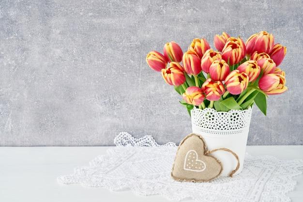 Красные тюльпаны в вазе с сердцем. день святого валентина копировать пространство