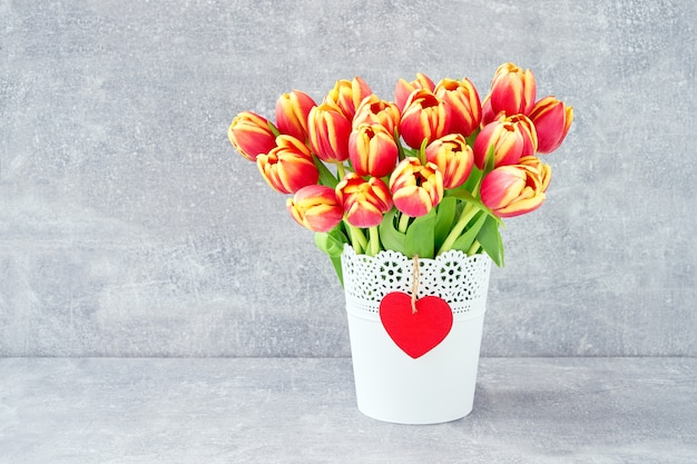 白い花の赤いチューリップ花束ポット灰色の背景に。休日の背景、コピースペース。