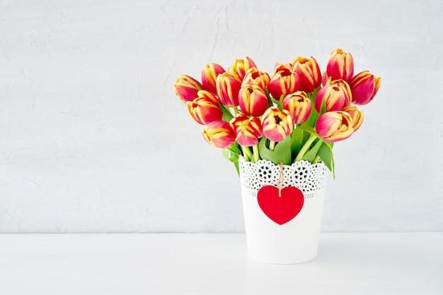 Букет красных тюльпанов в белой вазе, украшенной красным деревянным сердцем. день святого валентина концепция