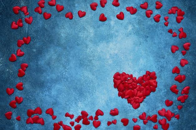 День святого валентина фон. красные сердца кадр на синем фоне.