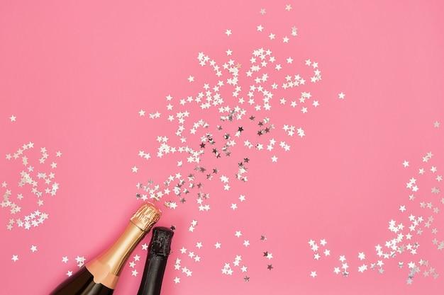 ピンクの背景に紙吹雪星とシャンパンのボトル。コピースペース、上面図