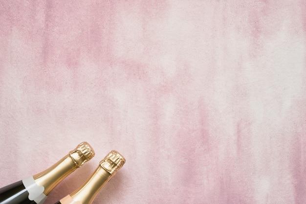 Бутылки шампанского на розовом фоне.
