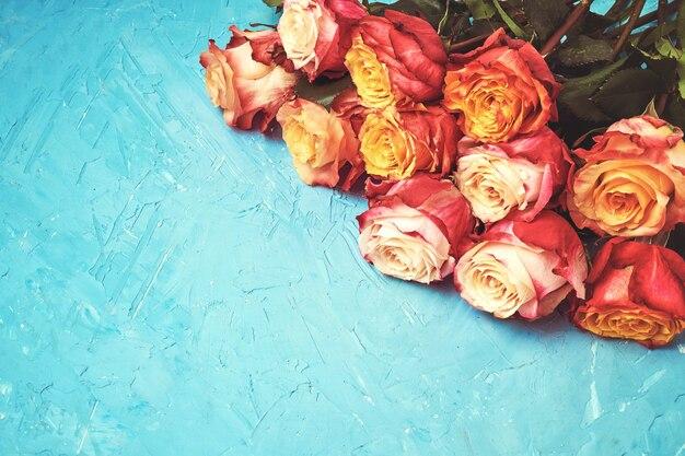 青の背景にカラフルなバラの花束。