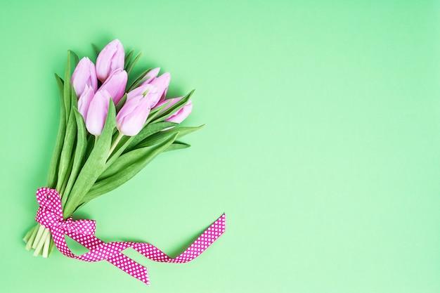 Розовый букет тюльпанов украшен лентой на зеленом фоне.