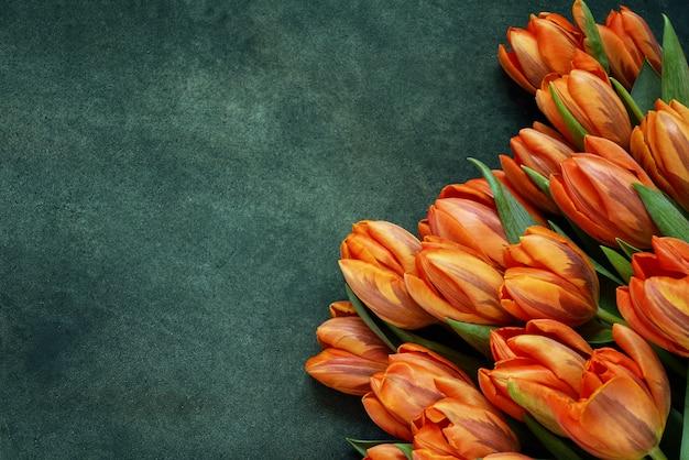 緑色の背景でオレンジ色のチューリップの花束
