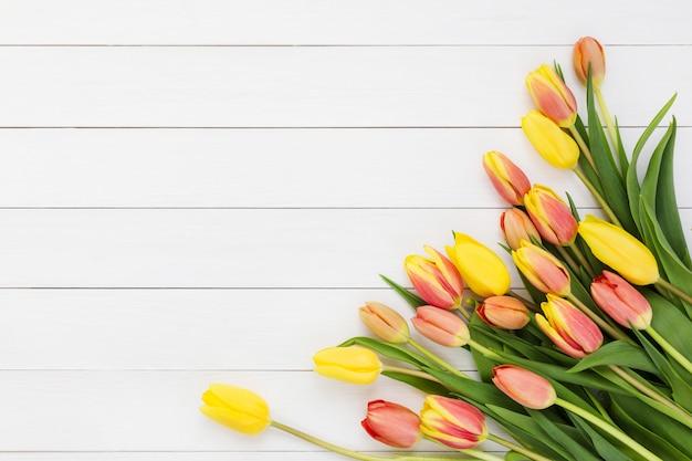 白い木製の背景に春のチューリップの花束。上面図、コピースペース