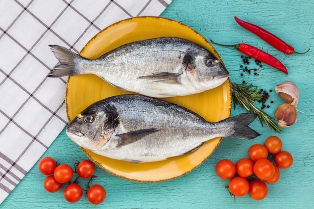 青の背景に皿の上の生の新鮮なドラド魚。上面図。