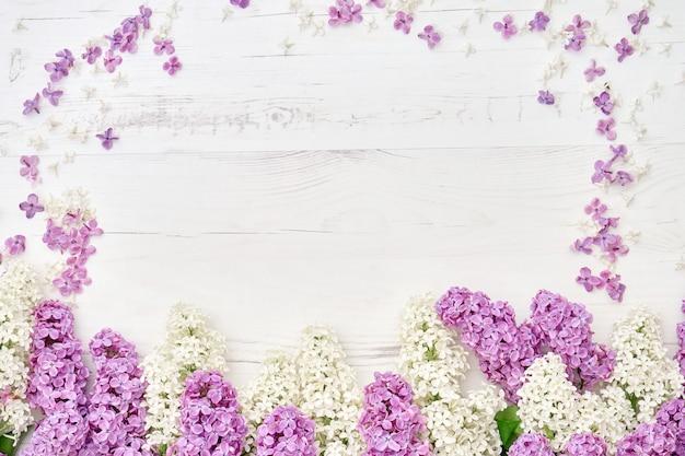 白い木製の背景にカラフルなライラック色の花の境界線。