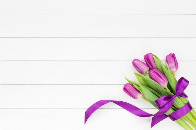 Букет из пяти тюльпанов с бантиком на белом фоне
