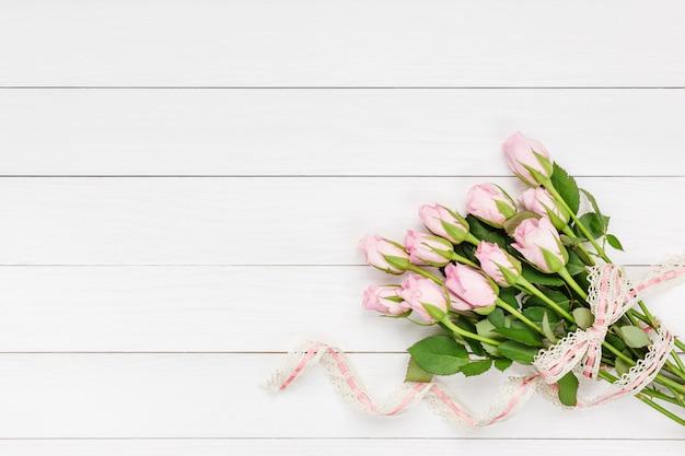 Букет из розовых роз украшен кружевом на белом фоне деревянные