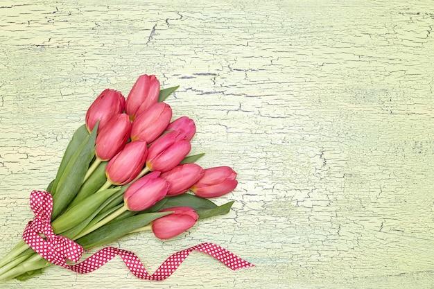 緑のリボンで飾られた赤いチューリップの花束