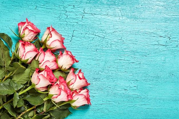 青い木にピンクのバラの花束
