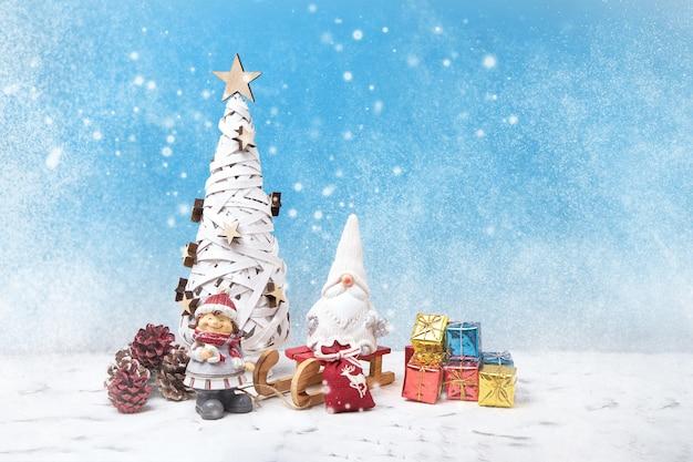 クリスマスグリーティングカード。クリスマスツリー、ノエルのノーム、小さな贈り物、雪の質感。クリスマスシンボル。