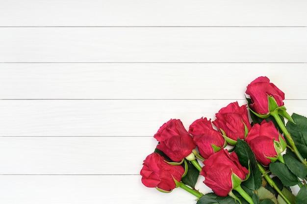 白い木製の背景に赤いバラの花束。