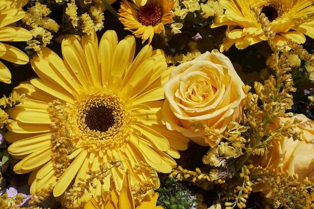 黄色の花の背景。黄色いバラとガーベラ。